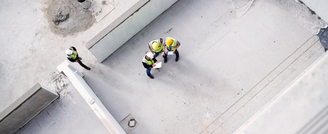 Overhead view of construction workers and engineers at construction site